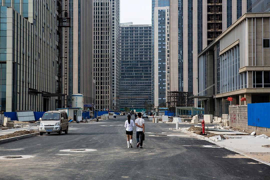 A couple walks down a street of empty office towers in the Yujiapu Financial District. - Tianjin