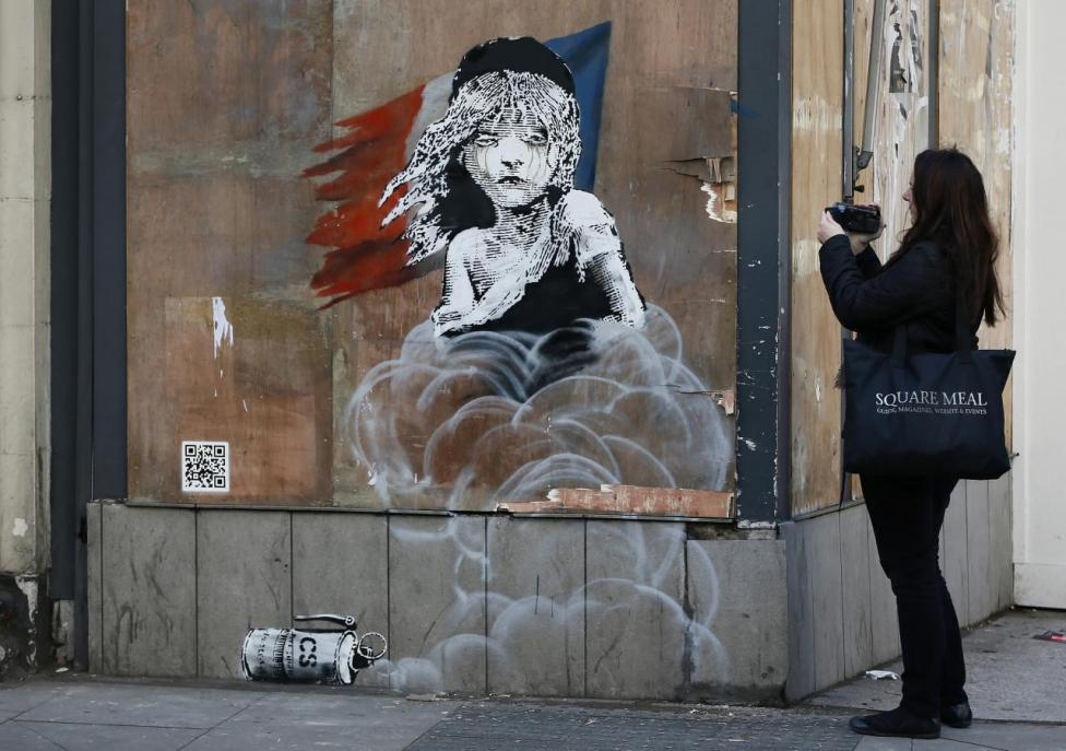 A woman films a new graffiti mural attributed to Banksy, opposite the French embassy in London, Britain January 25, 2016. REUTERS/Stefan Wermuth