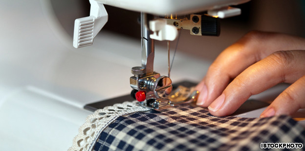 Hands work a sewing machine.