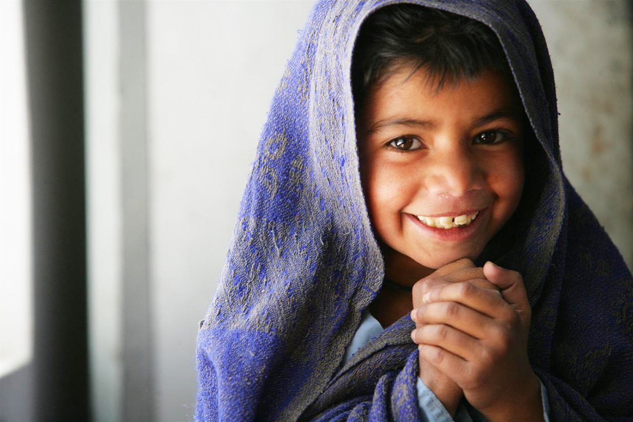 A girl wrapped in a blanket smiles and clasps her hands, at Model Primary School for Girls, a 'child-friendly' school in the village of Girani in Balochistan Province. UNICEF provides the school with educational and recreational supplies, hygiene kits, water and sanitation facilities and a teacher-training programme. In April 2006 in Pakistan, UNICEF assistance includes increased support for girls' education, the rehabilitation and reintegration of unaccompanied, orphaned, trafficked or exploited children; educational and vocational training for children who live or work on the streets; and support to child labourers and their families. UNICEF is also supporting the Government's 'Welcome to School' campaign to rebuild the education infrastructure and boost enrolment in areas affected by the 8 October earthquake that killed over 73,000 people, and left 3 million homeless. The campaign aims to enrol students, especially girls, in higher numbers than before the earthquake. UNICEF has supplied 'school-in-a-box' kits and helped set up more than 3,000 temporary schools, serving 260,000 children in the affected areas. Throughout Pakistan, UNICEF is assisting efforts to narrow the gender gap in education - one of the highest in the world - through community mobilization, including the introduction of 'child-friendly schools', teacher training and improvement of physical structures, with special emphasis on water and hygiene facilities for girls. Child-friendly schools promote free, compulsory education for all children in a safe, clean learning environment that engages parents and the community, and respects diversity and the rights of the child.